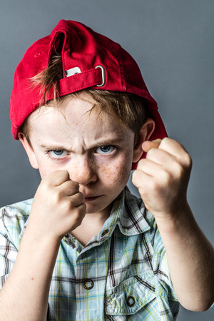 brat: aggressive 6-year old boy with freckles and a red hat back boxing with fists in the foreground,acting like a little bully at school, grey background studio