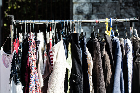 reusing: display of old fashioned womens clothes on hangers for reselling,recycling,donating,reusing or welfare for second life sold at flea market, outdoors Stock Photo