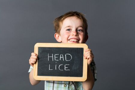 lice: laughing little child with red hair warning about head lice to fight against at school with writing slate as health shield, grey background studio