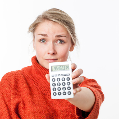 displaying: disappointed beautiful young female entrepreneur displaying a calculator in the foreground for symbol of savings or costs, isolated, white background Stock Photo