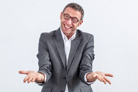 extrovert: joyous middle aged businessman with eyeglasses showing his empty flat hands in the foreground to show his success over white background Stock Photo