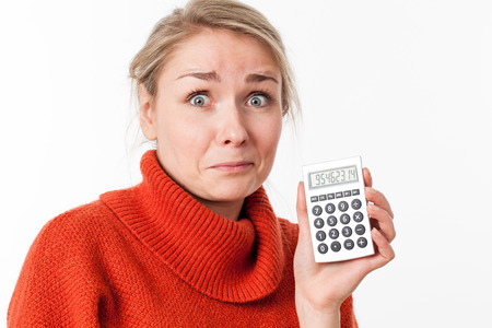eyes wide open: stunned young blond woman with eyes wide open, holding a calculator for symbol of maths or money, isolated, white background Stock Photo