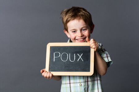 giggling: giggling preschool boy with red hair advertising on a school slate about poux written in French to face head lice, grey background studio