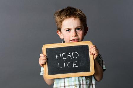 piojos: ni�o preescolar triste ocultar o proteger a s� mismo detr�s de una pizarra de la escuela como un escudo piojos de la cabeza para asustar y luchar contra el enemigo, fondo gris estudio