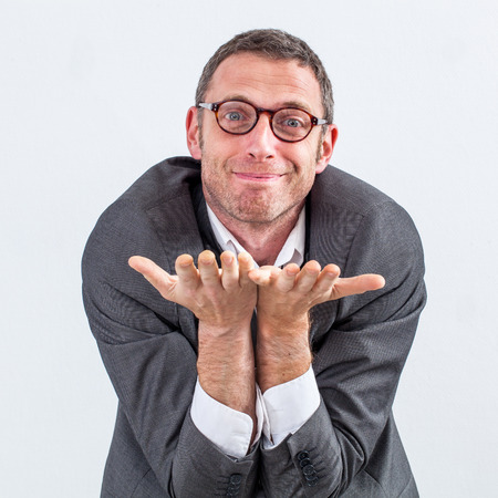 generosity: happy middle aged male manager begging or offering something on his empty hands in the foreground for kindness or generosity at work over white background Stock Photo
