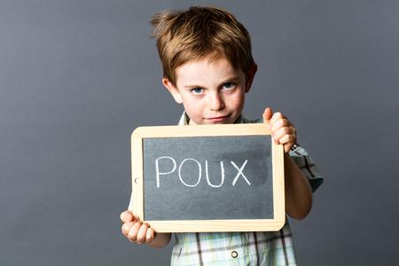 piojos: niño sonriente con el pelo rojo preescolar protegerse a sí mismo detrás de una pizarra de la escuela con 'poux' escrito en francés en él para hacer frente a los piojos de la cabeza, el estudio de fondo gris Foto de archivo