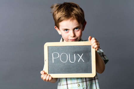 lice: smiling preschool kid with red hair protecting himself behind a school slate with poux written in French on it to face head lice, grey background studio Stock Photo