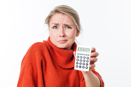 losing money: disgusted young blond woman frowning, holding a calculator, scared by maths or losing money, isolated, white background