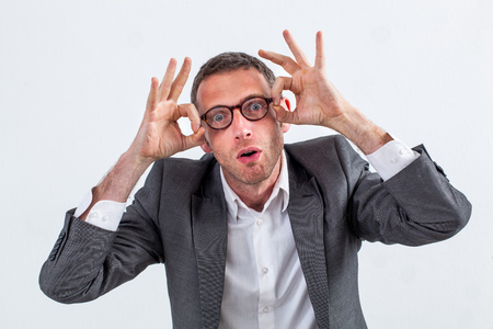 consternation: amazed middle aged businessman opening his eyes wide, acting dumb with surprising hand gesture for eyeopener or jaw dropping work over white background