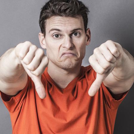 decepci�n: sulking deportivo hombre joven que muestra su disgusto y decepci�n con los pulgares abajo en el primer plano, primer plano de su rostro y un perdedor mala cara cartel con efectos de textura
