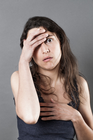 reassurance: lost young woman with long brown hair looking desperate and disillusioned, holding her head, touching her heart for reassurance, indoors Stock Photo