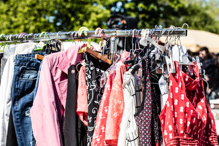 second hand: second hand pink and red fashion womens clothing on rack on sale at street fair or flea market for reselling or reusing, outdoors Stock Photo