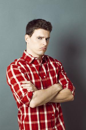 decepci�n: gru��n deportista joven deprimida con camisa a cuadros cruzando los brazos para la decepci�n, el aburrimiento o renuncia sobre fondo verde con efectos de contraste Foto de archivo