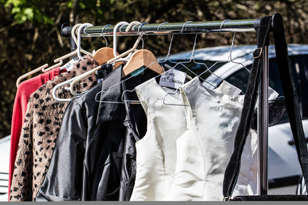 reusing: display of fast fashion womens dresses and jackets on rack for reselling,donation,reusing or thrift store for second life sold at flea market, outdoors