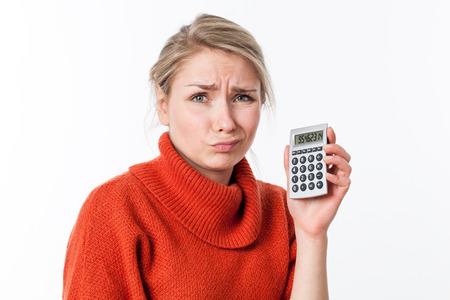 decepci�n: joven desilusionada mujer mala cara rubia, sosteniendo una calculadora para el s�mbolo de altos costos o decepci�n matem�ticas, aislado, fondo blanco
