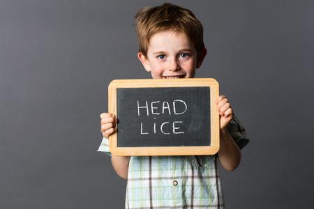 piojos: feliz ni�o peque�o con el pelo rojo informar sobre los piojos de cabeza a la lucha contra la diversi�n en la escuela, estudio de fondo gris
