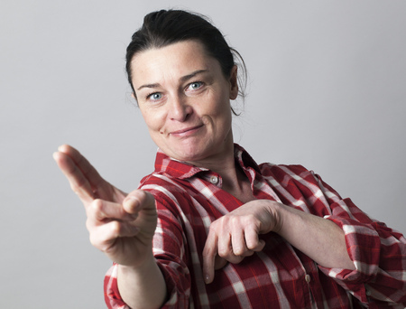 seduction: smiling beautiful middle aged woman showing her fingers like sexy guns in the foreground for female power and seduction concept, indoors Stock Photo