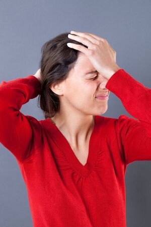 regret: upset young woman with eyes closed touching her forehead for mistake, headache or regret, indoors portrait