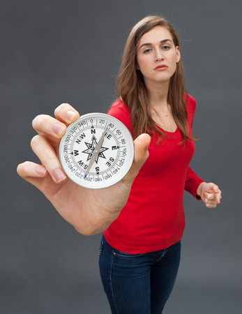 proud beautiful young woman with bossy and arrogant hand gesture showing an large compass, symbol of orientation, held in the foreground, grey background
