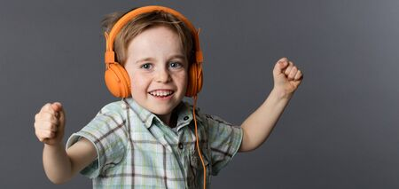 giggling: giggling young 6-year old red hair boy with freckles enjoying dancing with winning arms, listening to music on orange headphones, grey background