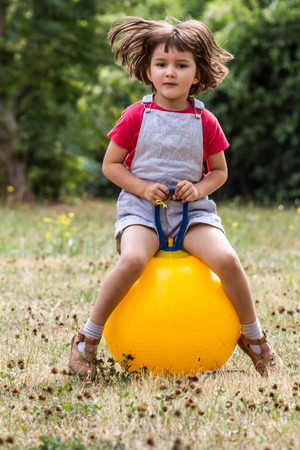 hopper: smiling young 4-year old kid jumping and bouncing on a hopper ball in dry summertime grass for fun and insouciance with green tree background Stock Photo