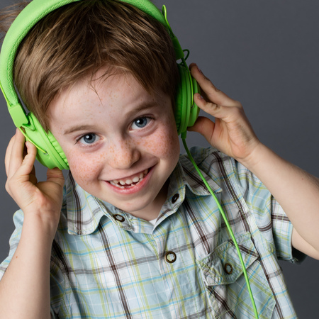 groovy: mischievous little 5-year old red hair kid with freckles laughing, listening to groovy music on green headphones, indoors Stock Photo