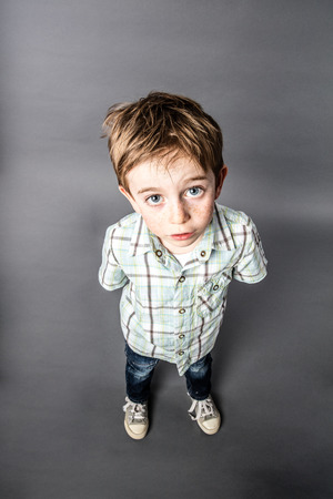 misunderstanding: stunned beautiful young 6-year old boy staring with wide-eyed standing for speechless surprise or misunderstanding, high angle view