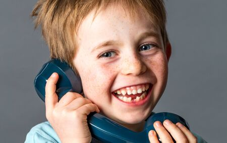 giggling: laughing young red hair boy with sparkling blue eyes, freckles and a tooth missing holding an old fashioned telephone giggling and talking, grey background studio Stock Photo