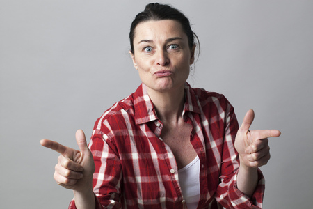 pouting: pouting beautiful middle aged woman aiming both fingers like sexy guns for female power and seduction concept, studio shot