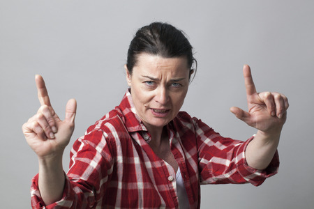 provoking: unhappy middle aged female rapper showing an aggressive hand gesture with fingers up like guns for manlike attitude Stock Photo