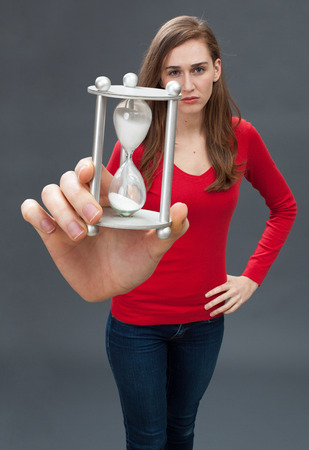 career timing: sad beautiful young woman standing with hands on hips, facing an egg timer in her oversized hand for focus on stressful deadlines in the foreground Stock Photo