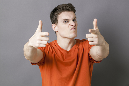 provoking: arrogant sporty young man showing an aggressive hand gesture targeting the foreground with both fingers like guns for violent attitude