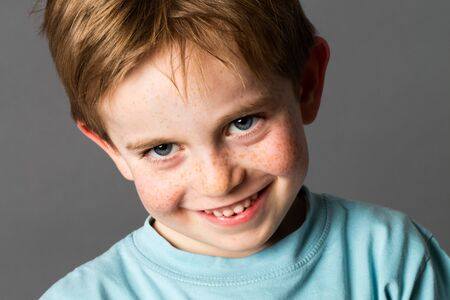 mischievous: closeup portrait of a young mischievous child with freckles and adorable blue eyes teasing and smiling, grey background studio Stock Photo
