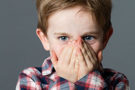 cheeky beautiful little 5-year old boy with fun blue eyes enjoying hiding his mouth for surprise or shyness, grey background