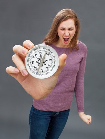 tantrum: enraged beautiful young woman having a tantrum, screaming against a big compass, symbol of orientation, held in the foreground