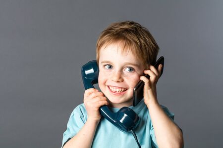 cheeky: cheeky young red hair boy talking on an old fashioned telephone and a smartphone on both ears for two voices communication, grey background studio