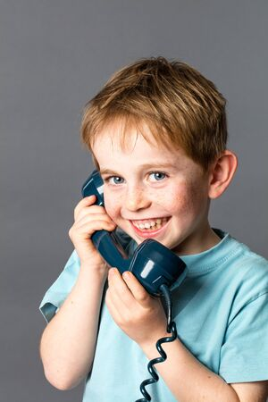 giggling: giggling 6-year old red hair boy with freckles talking on a blue old fashioned telephone for communication concept, grey background studio