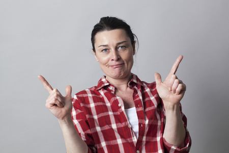 fake smile: playful beautiful middle aged woman showing both hands like sexy guns up for cowgirl power and self-assurance concept, studio shot
