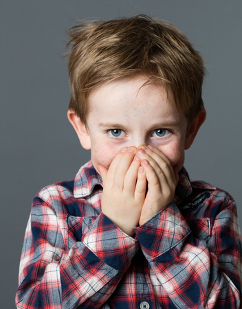 shyness: mischievous beautiful young 6-year old child with excited blue eyes enjoying hiding his smiling face for surprise or shyness, grey background