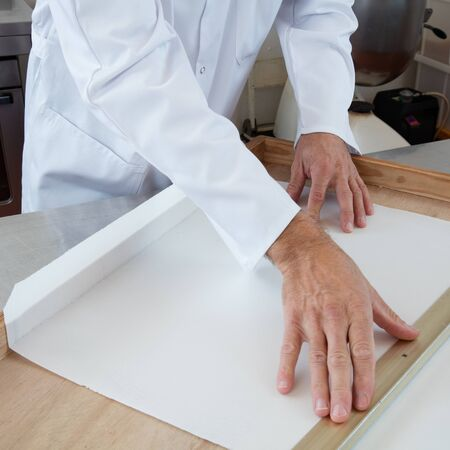 rice paper: professional hands preparing a wooden frame with rice paper as mold for nougat dough, French sweet craftsmanship specialty, in commercial kitchen