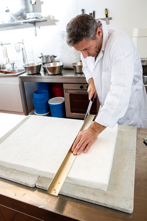 rice paper: cutting of final nougat made of Italian white dough with roasted almonds, honey and edible rice paper by pastry craftsman in industrial laboratory