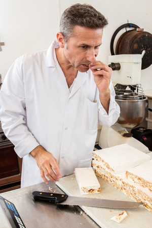 batch: professional nougat maker eating his fresh batch before slicing the French sweet almond specialty, commercial kitchen background