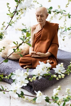 inner beauty: mindfulness concept - old yogi man sitting on towel and loofah with fresh white spring blossom flowers for meditation or inner beauty Stock Photo
