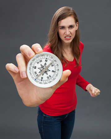 intimidating: angry beautiful young woman standing with fighting hand gesture, intimidating with an oversized compass, symbol of orientation, held in the foreground, grey background Stock Photo