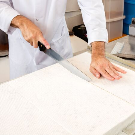 rice paper: cutting of hand-made nougat made of Italian white dough with roasted almonds, honey and edible rice paper by pastry craftsman in industrial kitchen