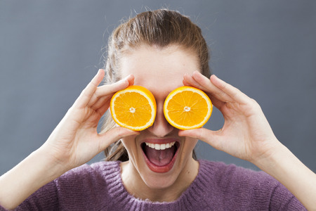 bubbly: funny beautiful young woman holding two orange slices on her eyes for radiant look or bubbly vitamin c, indoors Stock Photo