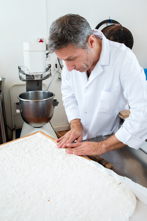 industrial kitchen: edible rice paper making of Italian white dough with roasted almonds for French sweet nougat specialty by male pastry cook in industrial kitchen