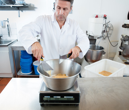 weighting: male cook weighting honey with a spatula, scaling sugar material is an industrial bowl for sweet nougat specialty, commercial laboratory background Stock Photo