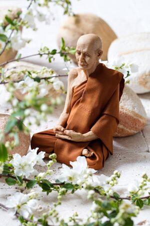inner beauty: mindfulness concept - calm old Hindu man sitting on white with beige limestone pebbles in fresh white spring flowers blossom for inner beauty and meditation
