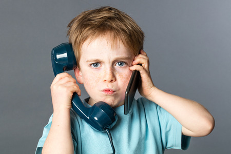 voices: unhappy 6-year old red hair kid listening to two voices on an old telephone and a new smartphone for burnout communication concept, grey background studio Stock Photo